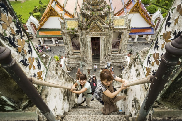 23 Sep 2013, Bangkok, Thailand --- Sept. 23, 2013 - Bangkok, Thailand - Tourists climb the stairs of the famous central chedi at Wat Arun on the last day the stupa would be open for climbing. The full name of the temple is Wat Arunratchawararam Ratchaworamahavihara. The outstanding feature of Wat Arun is its central prang (Khmer-style tower). The world-famous stupa, known locally as Phra Prang Wat Arun, will be closed for three years to undergo repairs and renovation along with other structures in the temple compound. This will be the biggest repair and renovation work on the stupa in the last 14 years. In the past, even while large-scale work was being done, the stupa used to remain open to tourists. It may be named ''Temple of the Dawn'' because the first light of morning reflects off the surface of the temple with a pearly iridescence. The height is reported by different sources as between 66,8 --- Image by © Jack Kurtz/ZUMA Press/Corbis